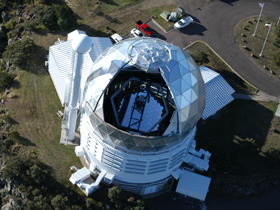 An aerial view of the Hobby-Eberly Telescope shows the current tracker, which is attached to the hexagonal frame, above the telescope's main mirror. [Martin Harris/McDonald Observatory]